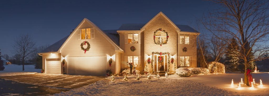 Special holiday decorated home with evening Christmas lighting, fluffy snow