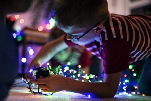 Little boy preparing Christmas lights on Christmas tree