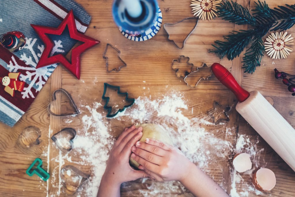 child baking christmas cookies on wooden table