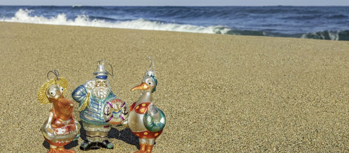 Sailor and migratory birds figurines on the beach, tropical ocean background, Christmas travel concept, copy space